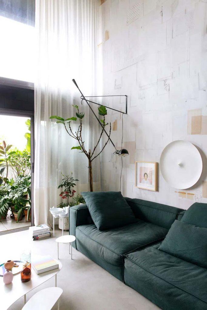 woonkamer hoog plafond architect nildo jose - In de woonkamer is de bank ontworpen door Nildo en het behang draagt de signatuur van Lucas Simões. De wandlamp aan de muur is de 265 wandlamp van Flos